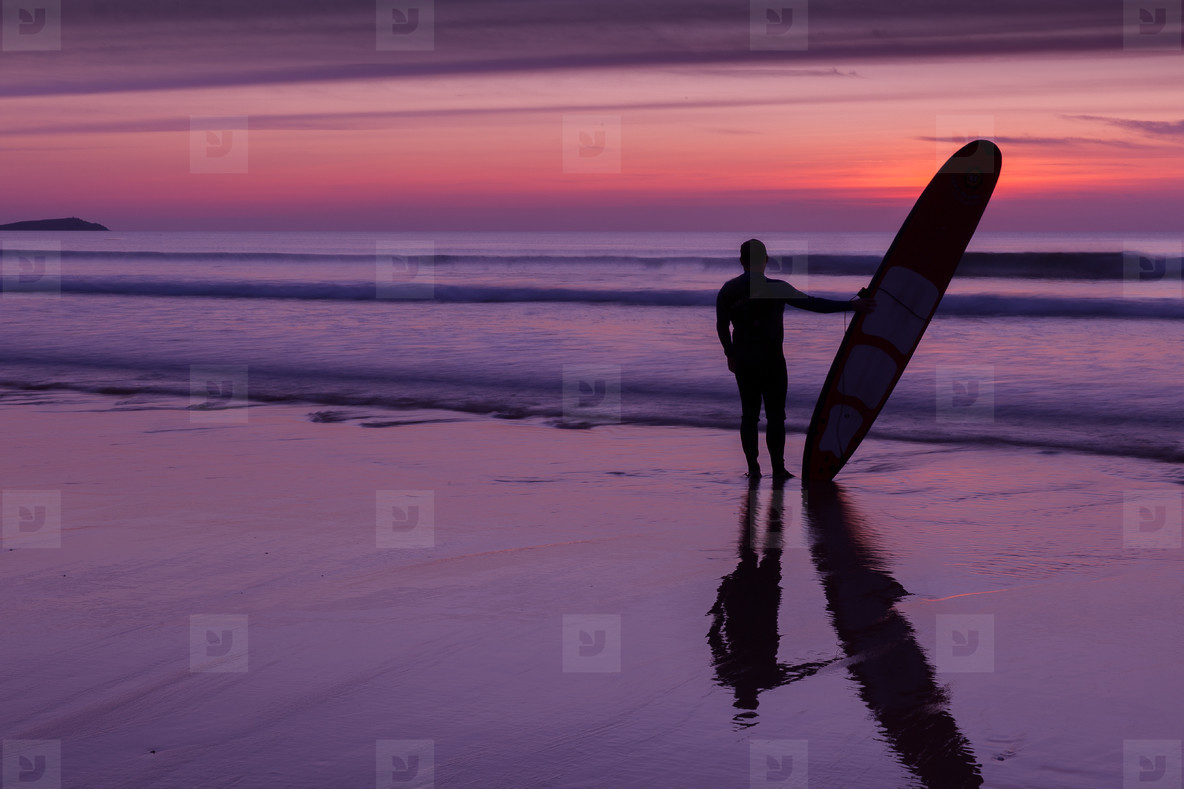 Surfer on beach at sunset