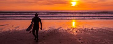 Surfer On Beach At Sunset