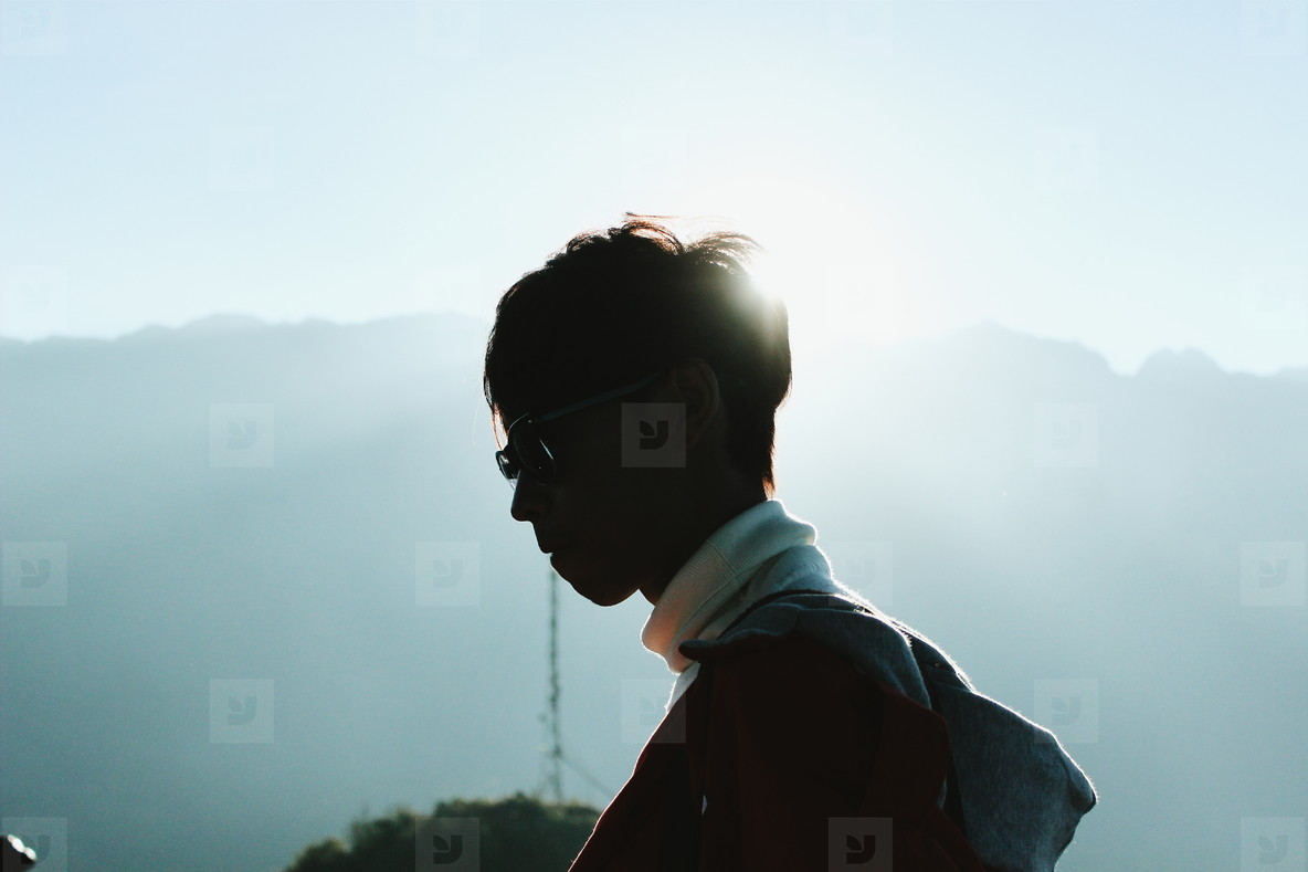 Young man standing with sunlight