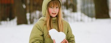 school girl with snow heart