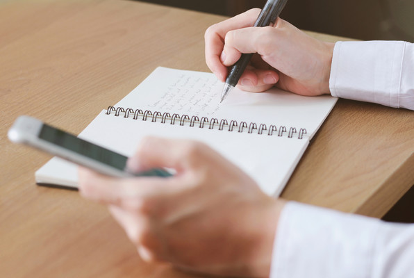 using smartphone and writing