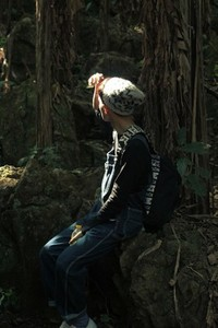 Young man sitting in forest