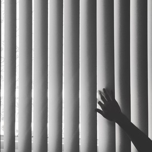 Hand touching blinds  BW