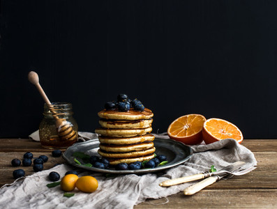 Pancake tower with fresh blueberries  oranges and mint on a rustic metal plate
