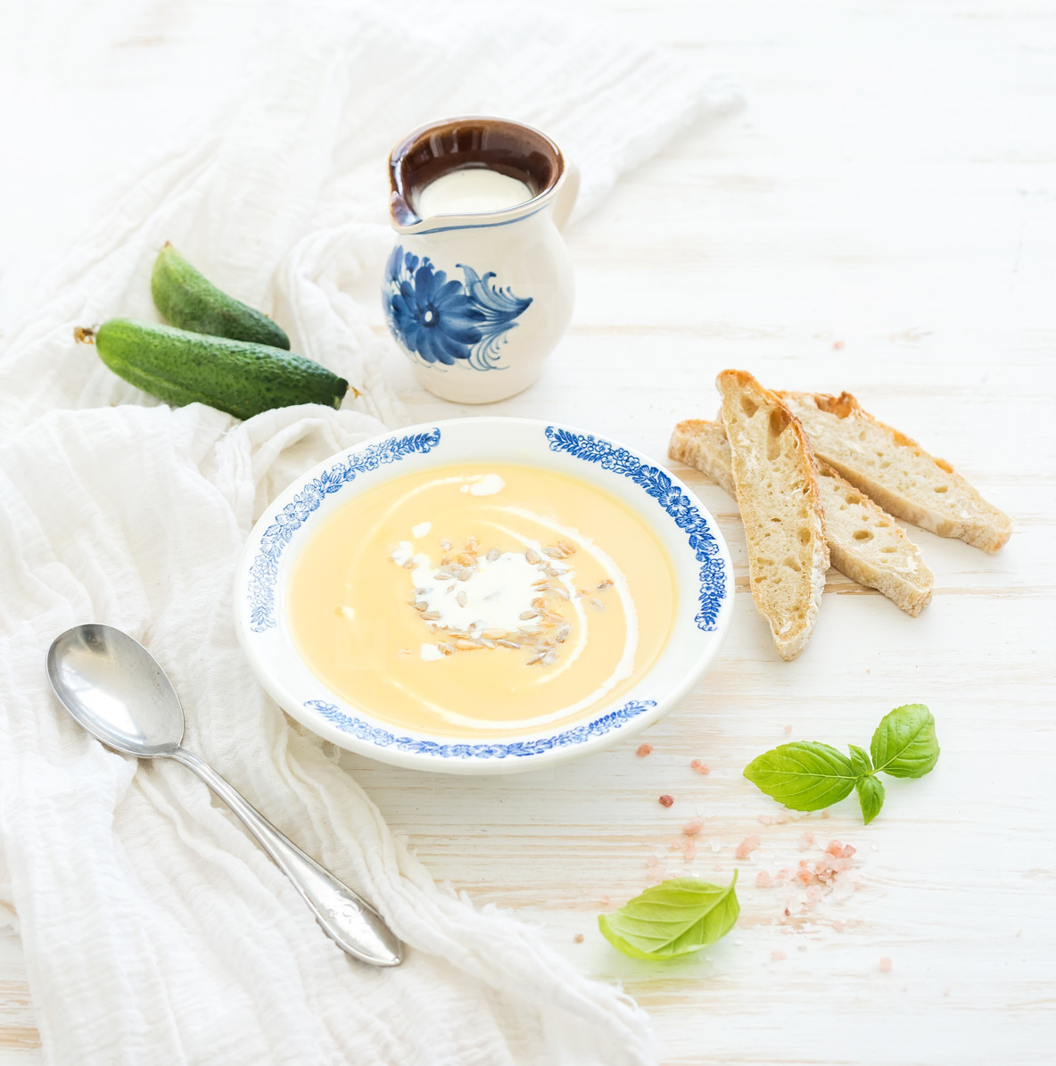 Pumpkin soup with cream  fresh basil  cucumbers and bread in vintage ceramic plate over white wooden background