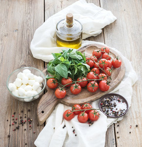 Basil cherry tomatoes mozarella olive oil  salt spices on rustic chopping board over old wood background