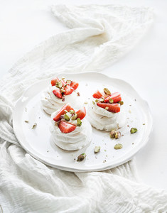 Small strawberry and pistachio pavlova meringue cakes with mascarpone cream fresh mint over white backdrop