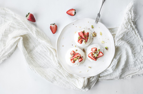 Small strawberry and pistachio pavlova meringue cakes with mascarpone cream