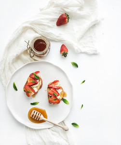 French toasts with strawberry  cream cheese  honey and mint on light ceramic plate over white backdrop