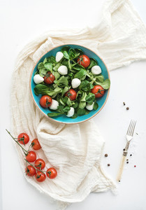 Spring salad with lamb s lettuce  mozarella and cherry tomatoes in blue ceramic bowl over white backdrop