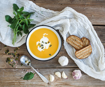 Pumpkin soup with cream  seeds  bread and fresh basil in metal plate on rustic wood background