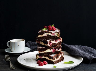 Brownies cheesecake tower with raspberries on white ceramic plate