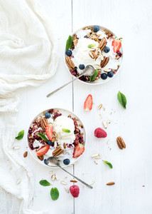 Healthy breakfast  Berry crumble with fresh blueberries  raspberries  strawberries  almond  walnuts  pecans  yogurt  and mint in ceramic plates over white wooden surface