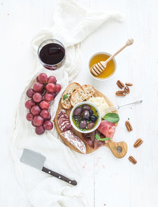 Wine appetizer set Glass of red grapes parmesan cheese meat variety bread slices pecan nuts honey olives and basil on rustic wooden board over white backdrop