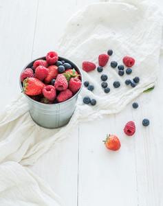 Metal bucket of strawberries  raspberries  blueberries and mint leaves  white wooden background