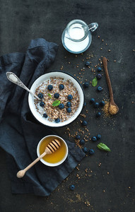 Rustic healthy breakfast set  Cooked buckwheat groats with milk  blueberries and honey on dark grunge backdrop