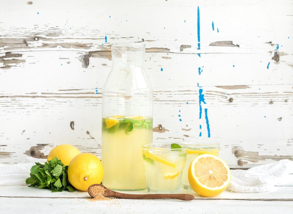 Fresh homemade lemonade with lemons and mint on white wooden background