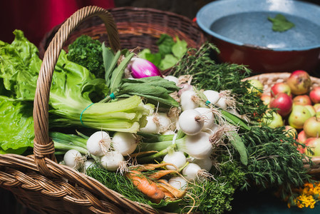 Fresh vegetables and herbs in rustic basket at Sunday market