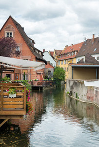 Colorful traditional french houses and a small restaurant terrace on the side of chanel Petite Venise Colmar France