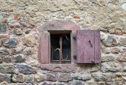 French window with closed old medieval wooden shutters in the village of Eguisheim  Alsace  France