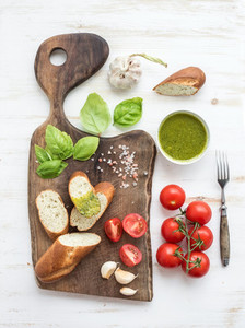 Pesto sauce  bread  cherry tomatoes  fresh basil and garlic on rustic walnut chopping board over white wooden backdrop