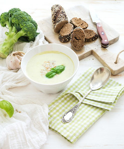 Broccoli cream soup with sunflower seeds fresh basil and bread in bowl over white wooden table