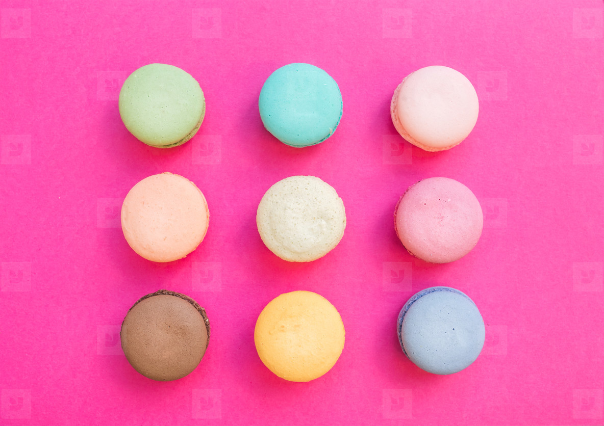 Sweet colorful French macaroon biscuits on bright fuchsia pink background