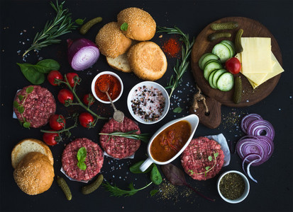 Ingredients for cooking burgers  Raw ground beef meat cutlets  buns  red onion  cherry tomatoes  greens  pickles  tomato sauce  cheese  herbs and spices over black background  top view