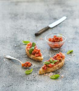 Tomato and basil bruschetta sandwich over grunge gray background