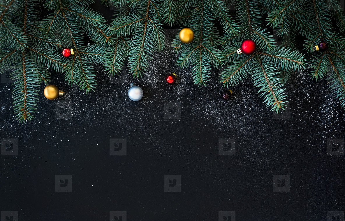Christmas or New Year decoration background  fur tree branches  colorful glass balls  on black grunge background