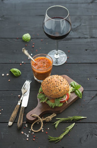 Fresh homemade burger on dark serving board with spicy tomato sauce sea salt herbs and glass of red wine over black wooden background