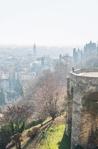 Woman standing at Venetian wall edge and watching the view of ancient italian town Bergamo