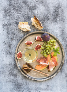 Wine appetizer set  Glass of white wine  honeycomb with drizzlier  figs  grapes  melon and prosciutto on silver tray over rustic grunge surface  Top view