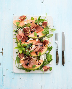 Prosciutto  melon  fig and soft cheese salad on a white serving board over grunge background