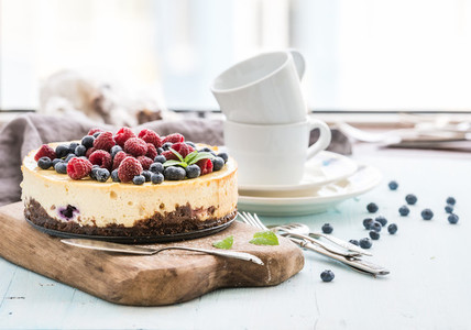 Cheesecake with fresh raspberries and blueberries on a wooden serving board  plates  cups  kitchen napkin  silverware over blue background  window at the backdrop