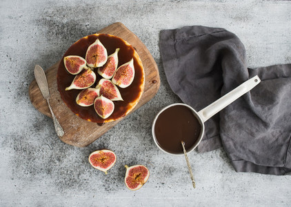 Cake with fresh figs and salted caramel on wooden serving board over grunge background