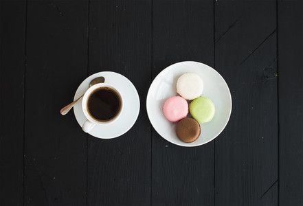 Macaron cookies  cup of espresso over black wooden backdrop