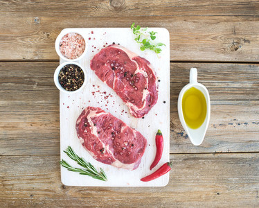 Raw fresh meat Ribeye steak entrecote and seasonings on white cutting board over grunge background