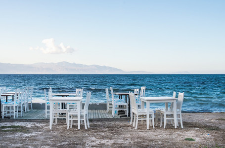 Chairs and tables in old cafe near the sea  Ciftlikkoy fishermen village  Aegean region  Turkey