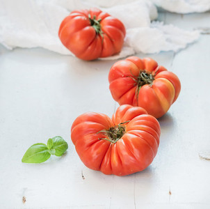 Fresh ripe hairloom tomatoes and basil leaves over light blue wooden background