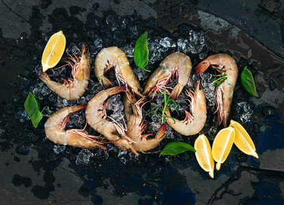 Fresh uncooked shrimps with lemon  herbs and spices on chipped ice over dark slate stone backdrop  horizontal