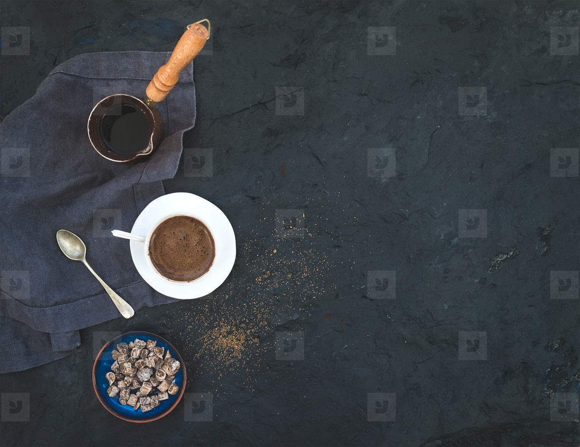 Cup of black coffee with dried figs and cane sugar over dark stone backdrop  top view