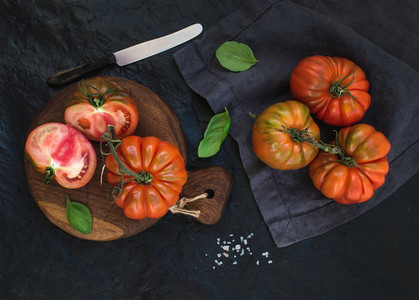 Fresh ripe hairloom tomatoes and basil leaves on rustic wooden board over black stone background  horizontal