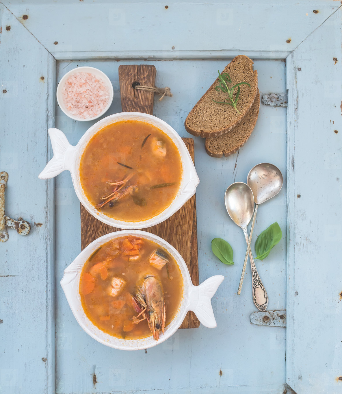 French Bouillabaisse fish tomato soup with salmon fillet  shrimp and spices on rustic wooden board over light blue background