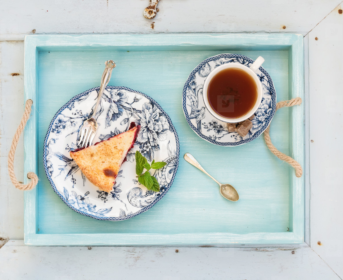 Piece of double crust plum pie and black tea in vintage porcelain cup  blue wooden tray  Top view  horizontal