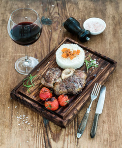 Roast beef Ossobuco with rice  vegetables and glass of wine on serving board over rustic wood background