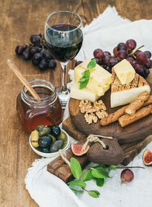 Glass of red wine  cheese board  grapes fig  strawberries  honey and bread sticks  on rustic wooden table