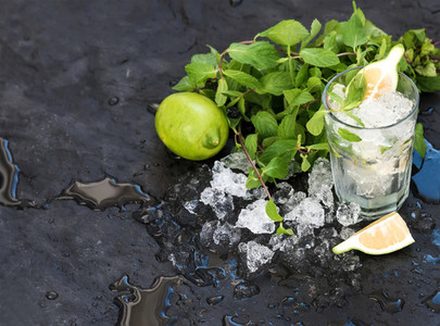 Mojito cooking set  Bunch of fresh mint  lime  chipped ice and coctail glass over black slate stone backdrop  copy space