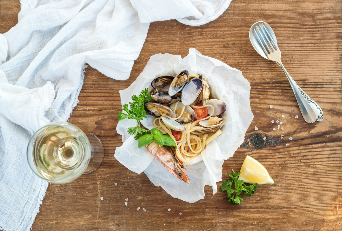 Seafood pasta  Spaghetti with clams and shrimps in bowl  glass of white wine