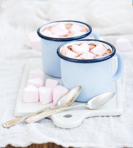 Seint Valentines holiday greeting set Hot chocolate and heart shaped marshmallows in old enamel mugs on white ceramic serving board